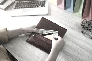 A person is taking both a $100 bill and a credit card out of a wallet