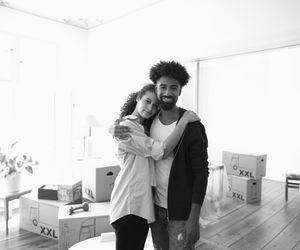 A young couple takes a break from unpacking in their new home.
