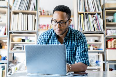 person with glasses in blue flannel shirt working on laptop