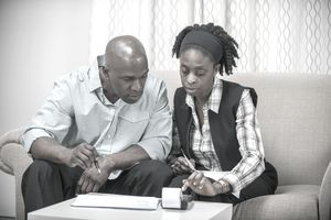 A couple seated on a sofa with paperwork and a calculator