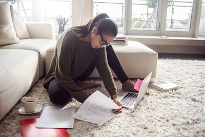Young woman in glasses reviewing paperwork on the floor of her living room with laptop.