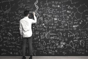man writing math formulas on chalkboard
