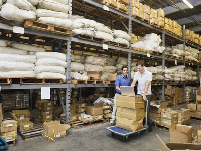 Business owners calculating inventory turnover in a warehouse