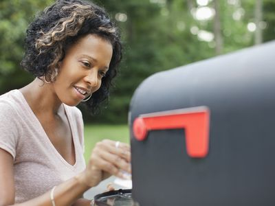 Woman taking mail from mailbox