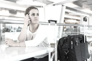 female traveler on cell phone in airport