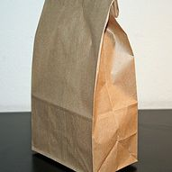 A brown bag lunch with a rolled top ready to go to office or to school