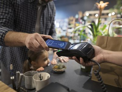 Close up father and daughter paying with smart phone contactless payment at plant shop counter