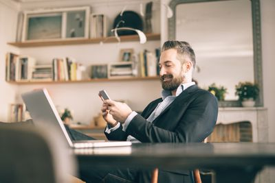 Man smiling as he watches stocks on his smartphone