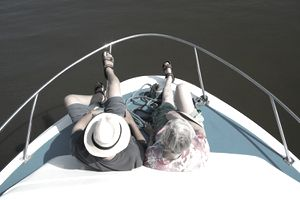 A retired couple sits on the bow of a boat.