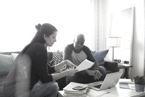 Couple sitting on a sofa with a coffee table holding files and a laptop balancing their checking account