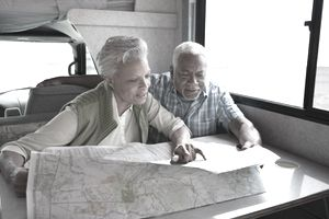 Retired couple reading a map in an RV and plotting their route.