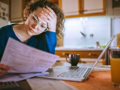 A worried woman at a kitchen table reviews the small print on her student loan application. There's an open laptop on the table, partially obscured by the paperwork she holds. A ceramic cup sits left of the laptop keyboard and glass of orange juice sits to the right.