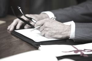 A man's hands holding a pen and glasses atop a file folder and documents
