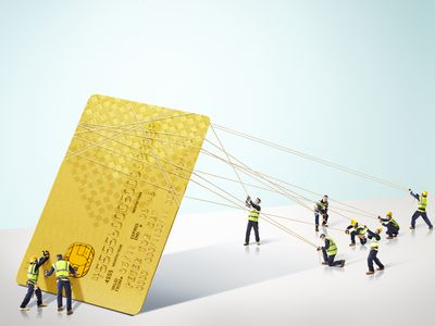 Group of builders hoisting up a giant credit card, to symbolize how a secured card will rebuild bad credit