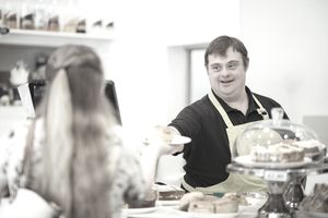 A person with Down syndrome serving a scone to a woman in a cafe where he works