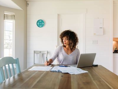 A woman sits at her dining room table with laptop and tax paperwork