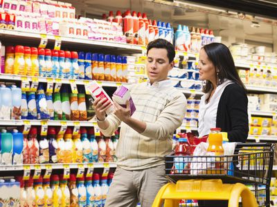 Man and woman comparing two brands of a product in the grocery store