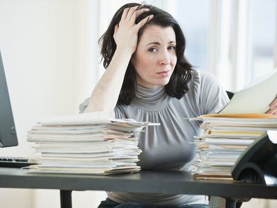 Frustrated woman holding her head in her hand looking at her student loan statement
