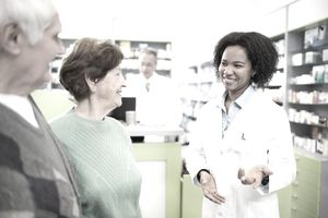 African American pharmacist communicating with senior couple in a pharmacy.