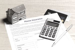 Blank homeowner insurance document with a model home, credit cards, and calculator.