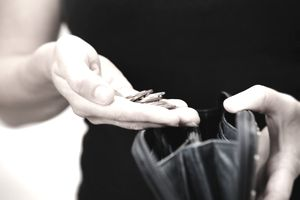 Woman holding loose change over an open purse