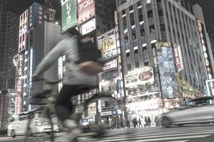 Cyclist driving on busy road in Tokyo