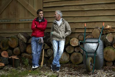 Father and son standing beside a woodpile outside a barn