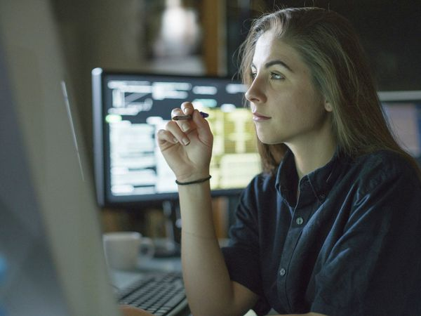 Young woman is seated at a desk surrounded by monitors displaying data