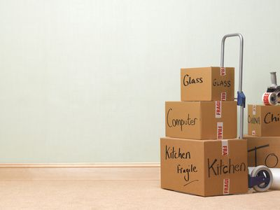Moving boxes, packed, labeled and stacked on a dolly with moving tape and wrap