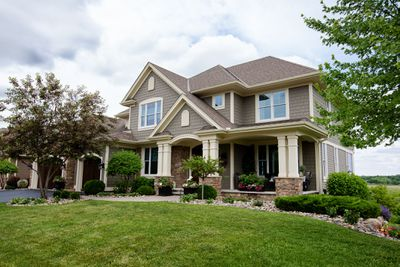 Pewter and white-trimmed large suburban house and yard.