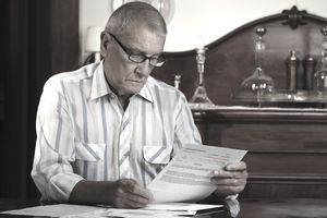 Elderly man sitting at a desk looking through bills