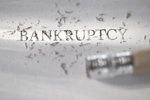 Studio shot of pencil erasing the word bankruptcy from piece of paper.