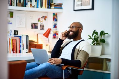 Cheerful businessman working from home on phone.