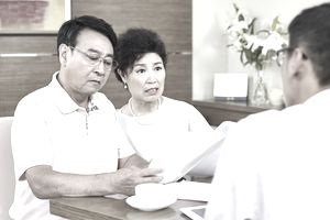 senior asian couple shocked while reading a contract