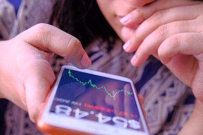 young business women analyzing stock market trend on phone