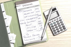 Calculator, pen, and notepad showing a monthly budget missing a pay yourself first line item