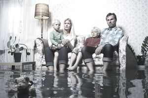 Family sitting on couch in flooded living room concerned because they self-insure instead of buying traditional homeowners.