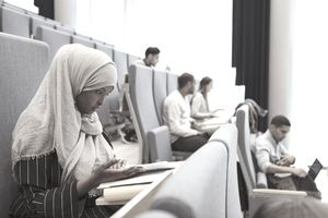 Serious woman in hijab reading book and other students in the background in a university lecture hall.