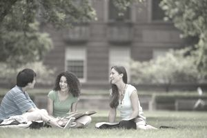 Three university students with books sitting in a group on a grassy lawn outside of a brick building
