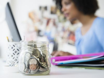 Woman working on a laptop on a desk with a small jar of change as a rainy day fund.