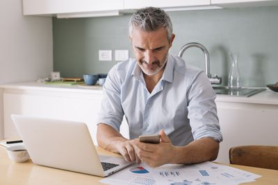 A person using his phone and computer to complete business