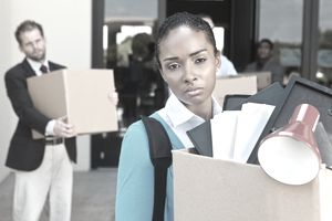 Angry and sad workers carring boxes of possessions leave an office building after being laid off