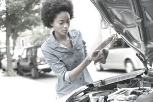 Woman checking the oil dipstick in her car