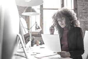 Businesswoman reading document in creative office