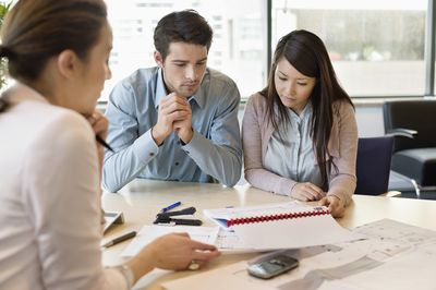 Real estate agent discussing property documents to clients