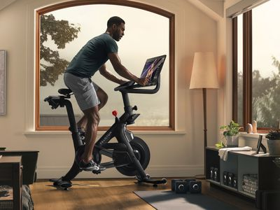 A Black man works out on a Peloton stationary bicycle.