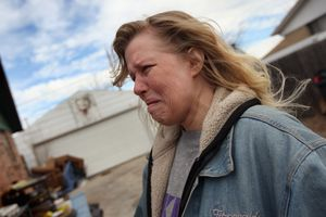 Tracy Munch watches as an eviction team removes furniture from her foreclosed house
