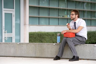 Man eating lunch on a ledge by an office building