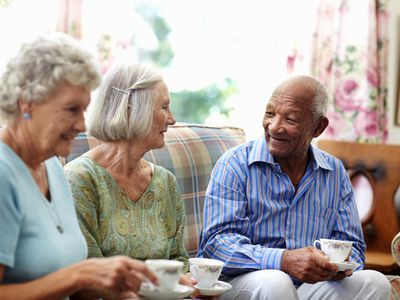 Three older people on a couch enjoying a cup of tea