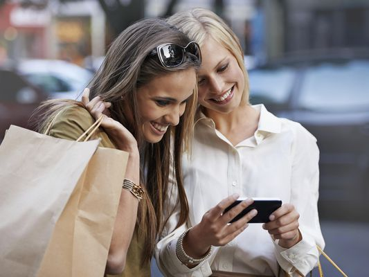 two women shopping and checking phone